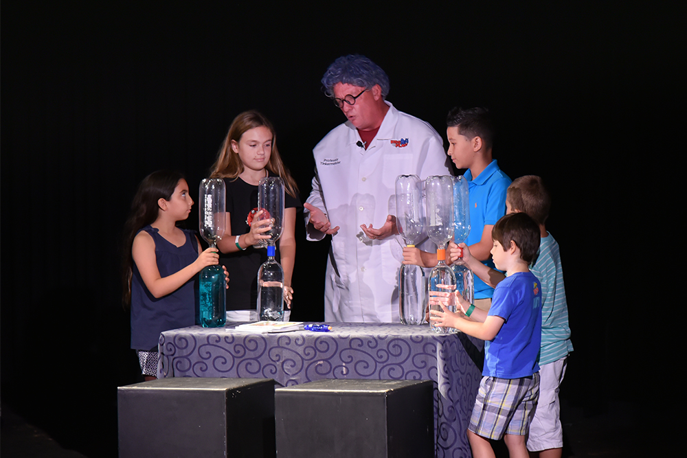 An enthusiastic scientist leads a group of children in a scientific experiment.