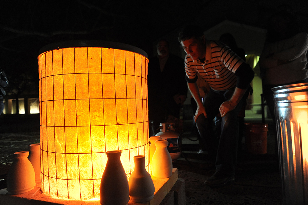 A man crouches down to get a better view of a glowing kiln at a museum event.