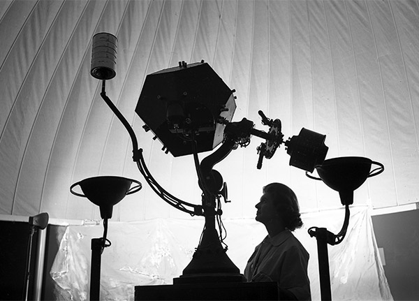 The silhouette of a woman standing with the original planetarium projector