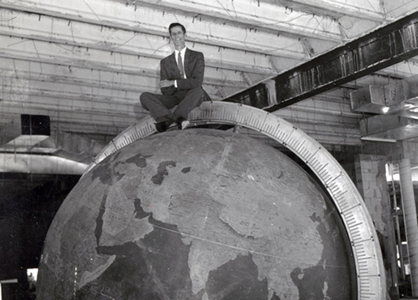 A man sits criss-cross legged on top of the large globe at the old museum location, before it was fully installed.