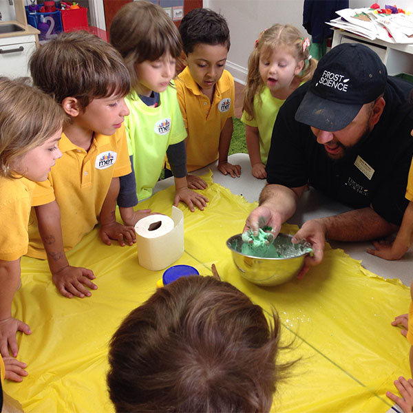 A Frost Science employee demonstrates an experiment to an onlooking group of children.