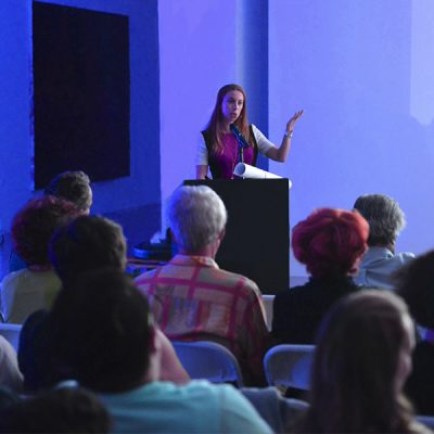 A woman stands at a podium, addressing an attentive audience.