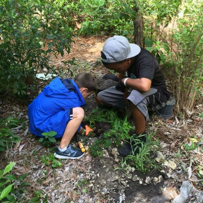 Two young boys help the volunteer effort by planting trees.