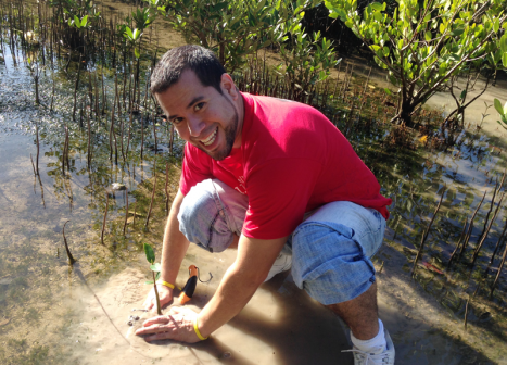 A Wells Fargo Green Team volunteer smiles for the camera as he plants a mangrove in shallow water and mud.