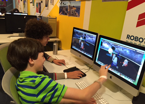 Two young boys compare computer screens to discuss their virtual simulations.