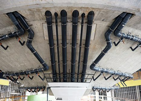 Large pipes run along a concrete panel.