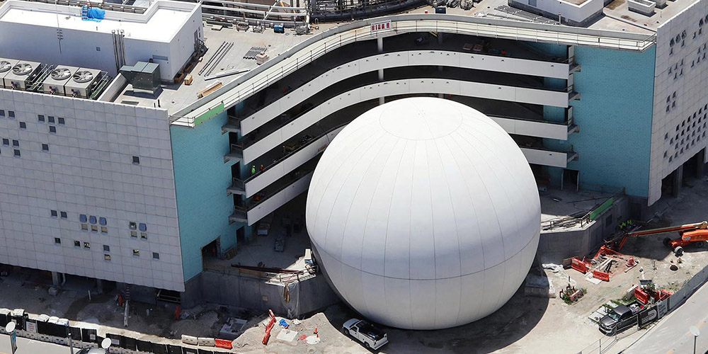The white exterior of the finished planetarium shines in the sunlight.