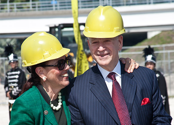 Dr. Phillip Frost and Patricia Frost pose happily in yellow hard hats at the new museum construction site.