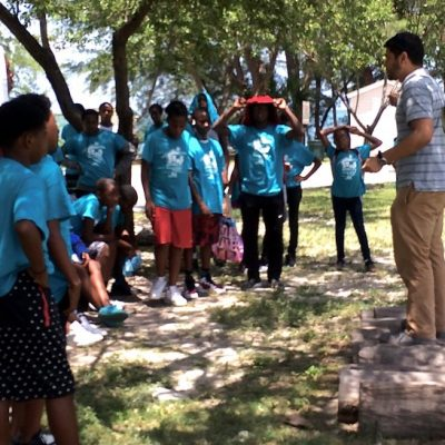 Man leading a discussion with students from the Overtown Youth Center on how to reduce, reuse and recycle.