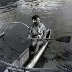 Native woman on a canoe.