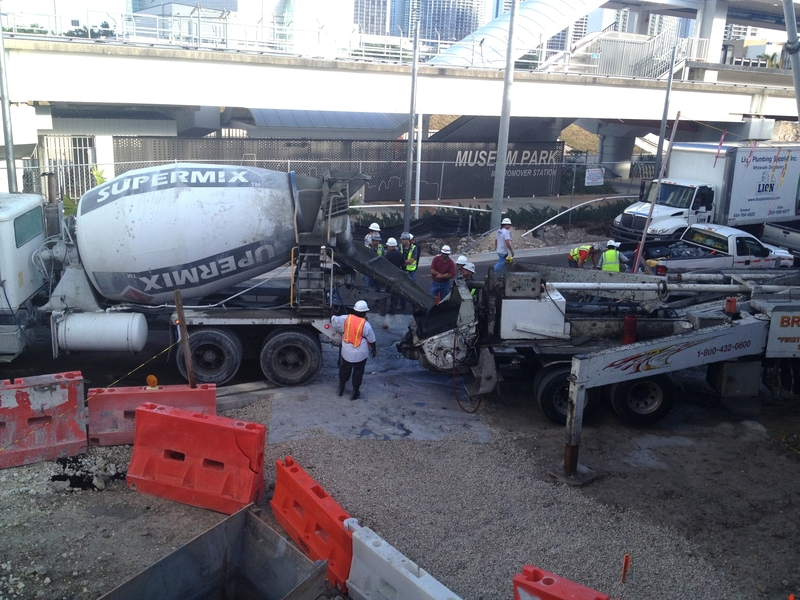 A concrete mixing truck pouring into a concrete pump, which will transport the concrete into the planetarium dome molds