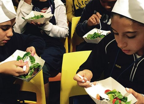 A group of young girls eats the healthy salads that they helped to prepare.