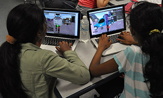 Two girls in the GROOVE program sit at laptops and work to create their virtual simulations.