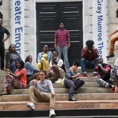 A group of Upward Bound students sits on a set of steps on a regional college tour.
