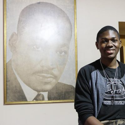A young African American man smiles proudly next to a portrait of Martin Luther King Jr.