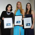 Three women posing for a photo while holding their awards.