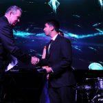 Young man accepting the Upward Bound Merit Award