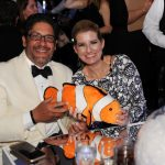 Adults posing for a photo with a stuffed clown fish
