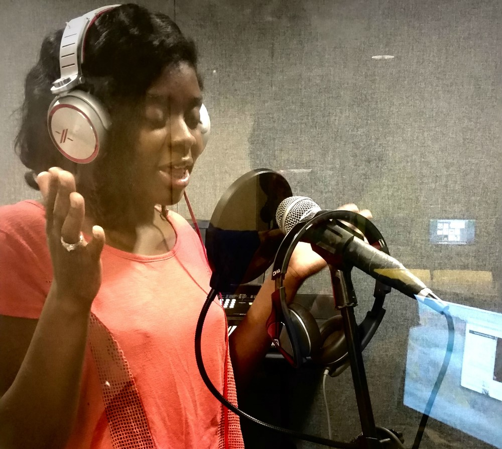 "Young woman recording her original poem, ""Onslaught,"" on equipment provided by Best Buy."