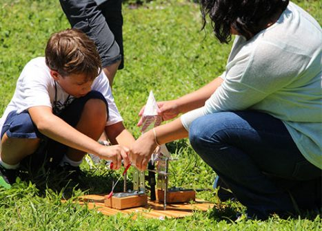 A young boy works with an adult to set up a backyard rocket launch.