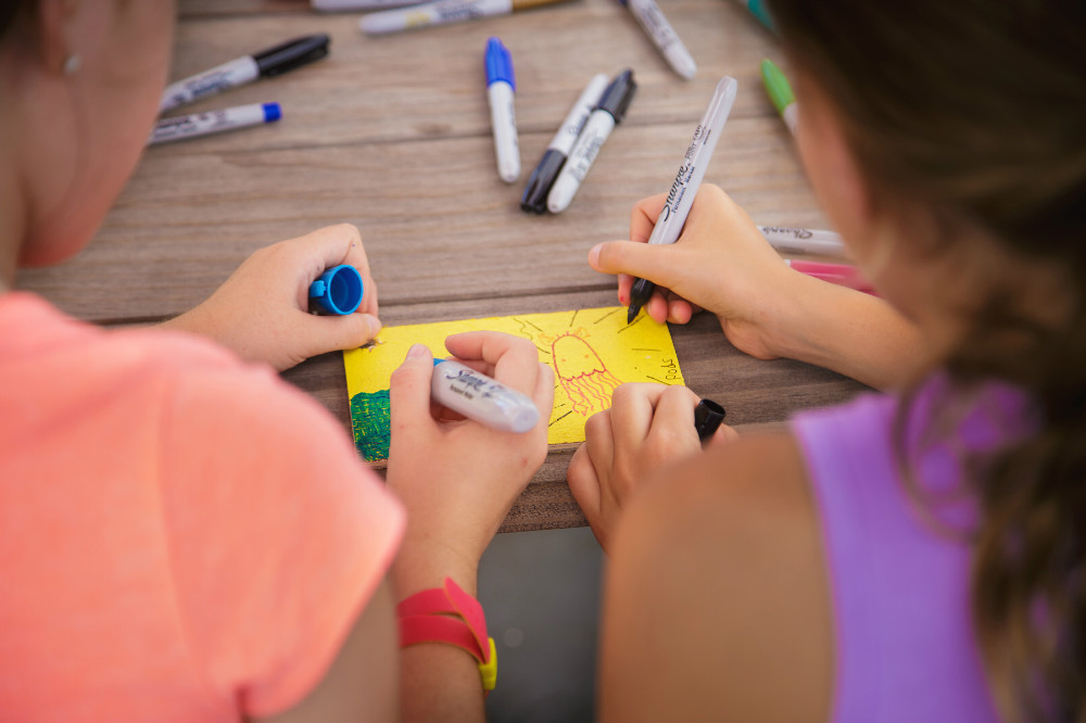 Two young girls creating an art piece