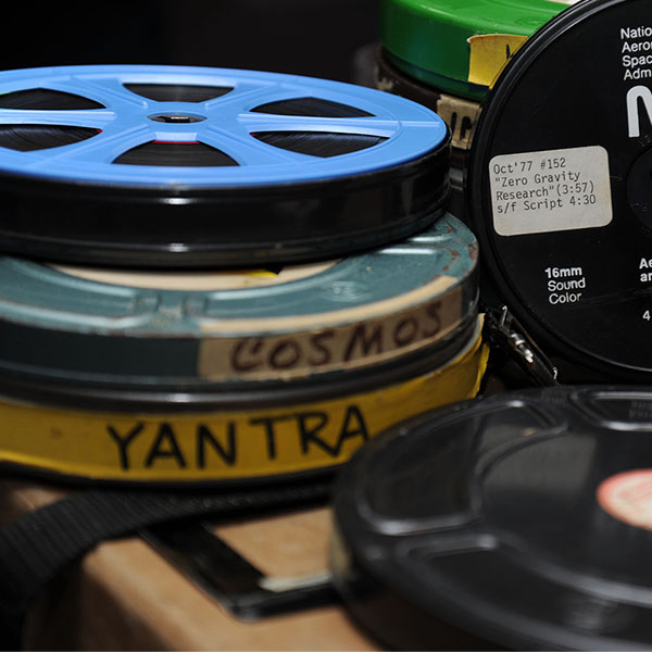 A stack of labeled film cannisters and reels sits on a table.