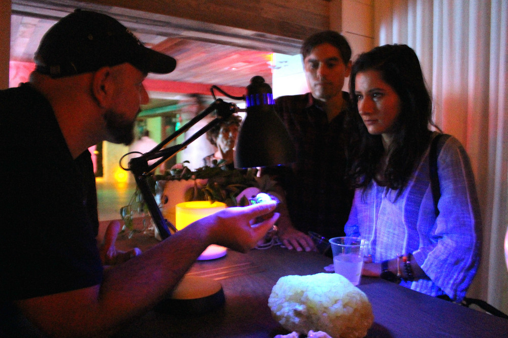 Community Engagement Manager showcases minerals that fluoresce under long-form ultraviolet radiation