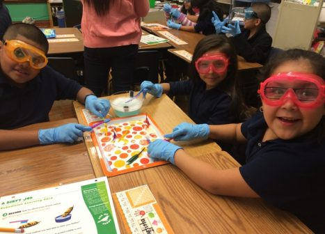 Two young Latino girls in bright pink goggles work on a dissection.