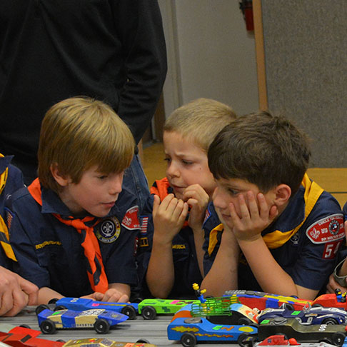 Young boy scouts observing small toy cars
