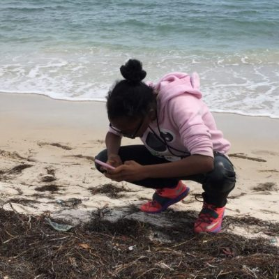 Young girl taking photo of beach pollution