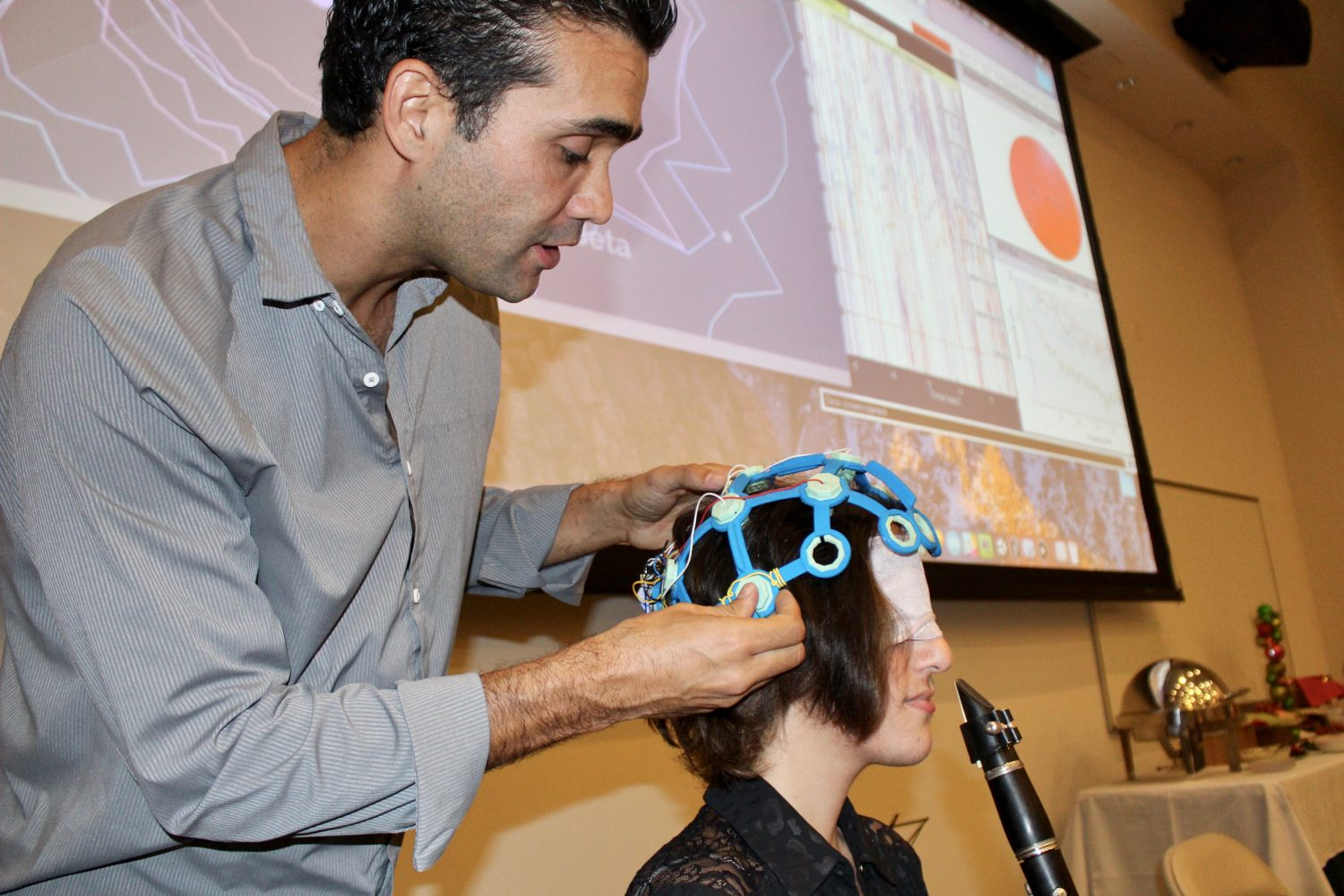 Man placing scientific equipment on woman's head