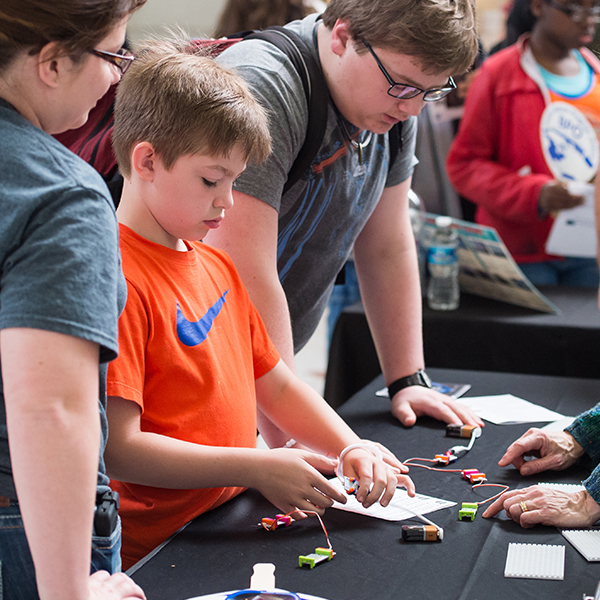 An attendee of NASA's Earth Day event conducts an experiment with circuits