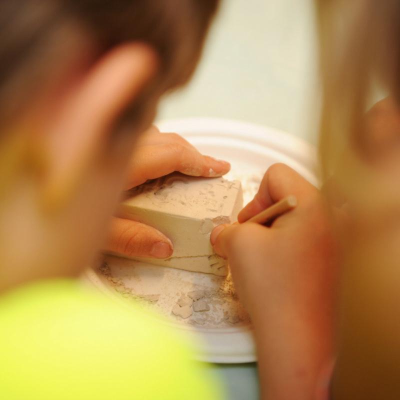 kids work on unearthing a dinosaur