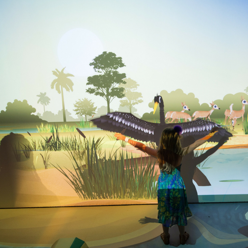 girl playing against the projection of a bird inside the river of grass