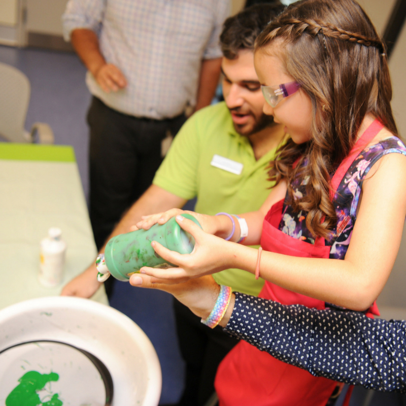 child is helped by party host to pour paint into spin art machine