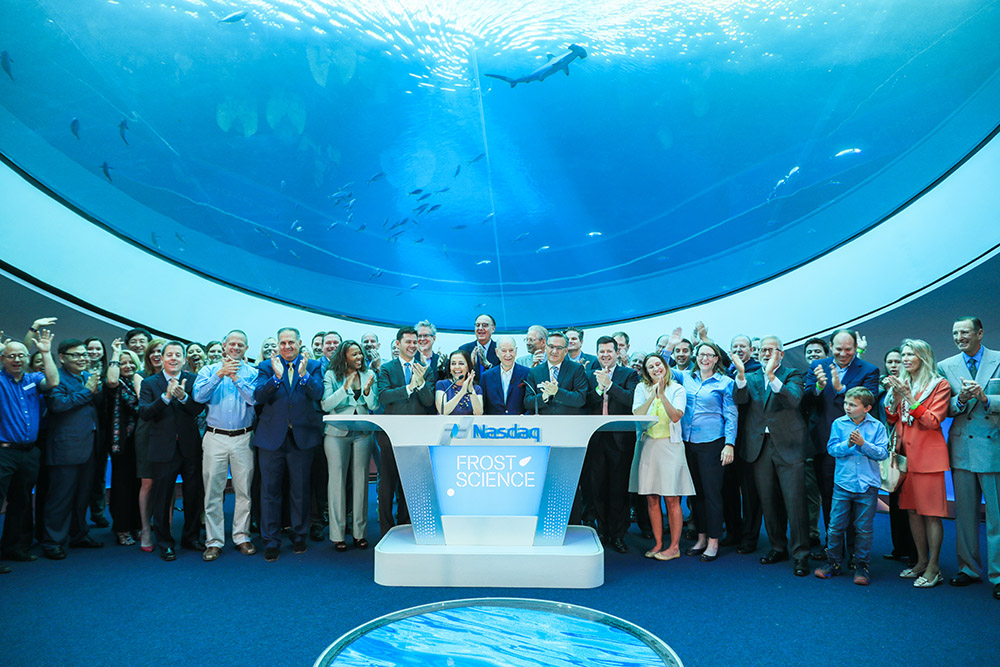 Group of adults posing for a photo in front of an aquarium