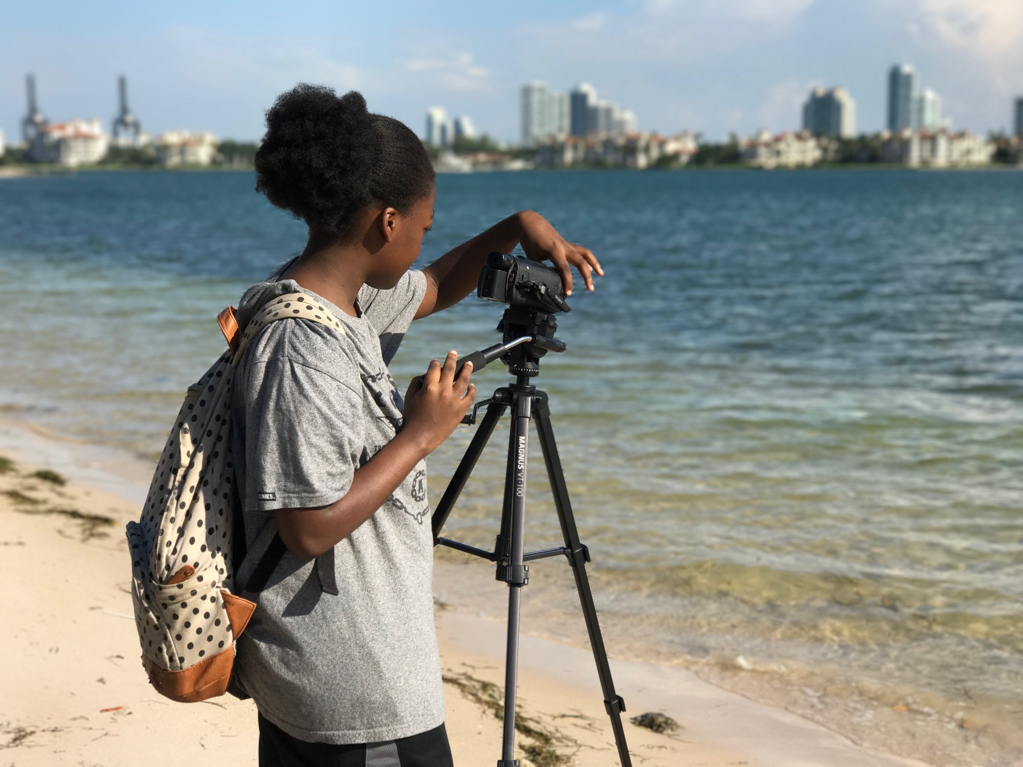 Young student operating a camera in front of the water