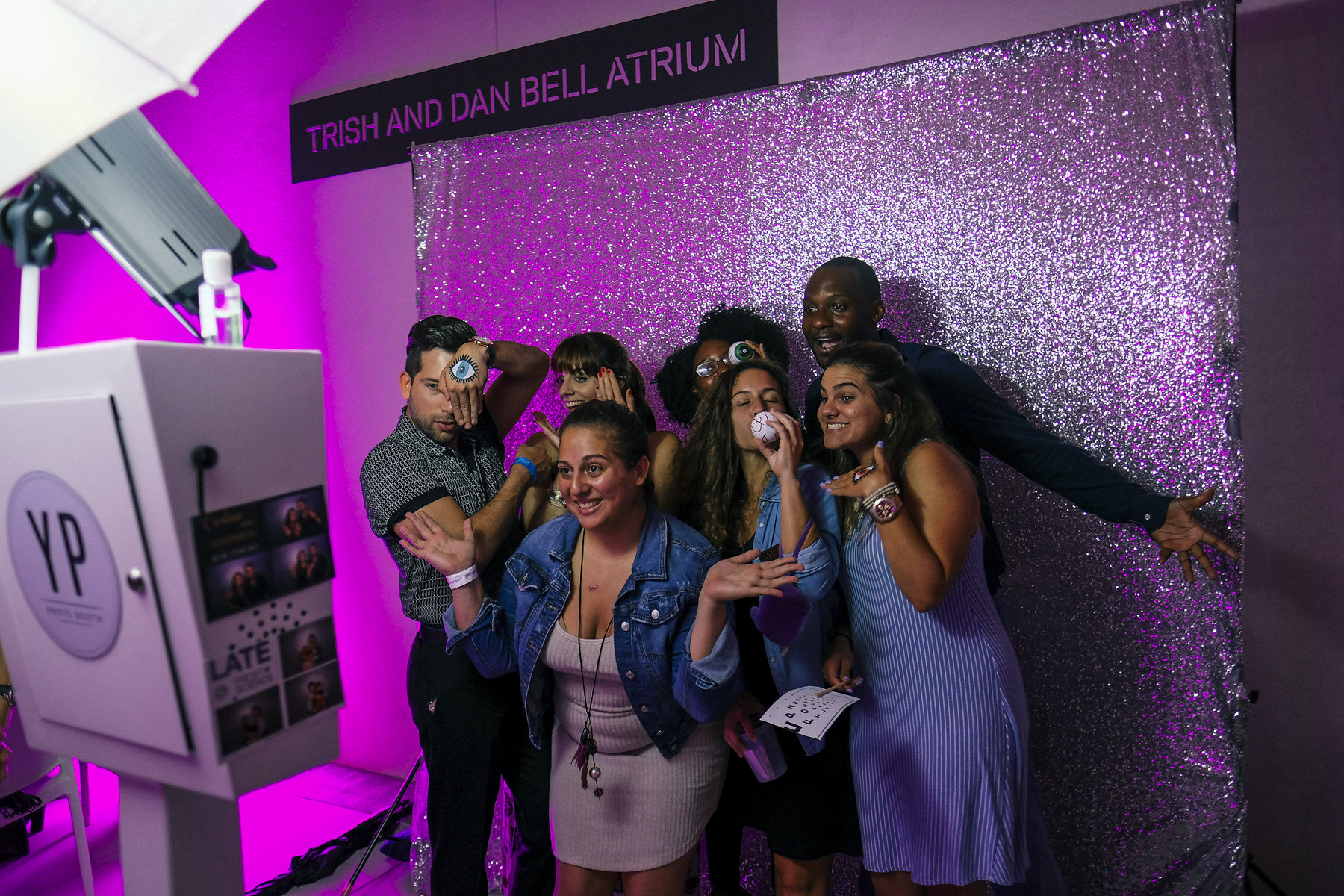 Young adults posing for a photo in a photo booth