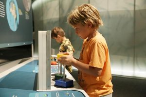 two young boys playing with a brain activity in Brain: The Inside Story exhibit.