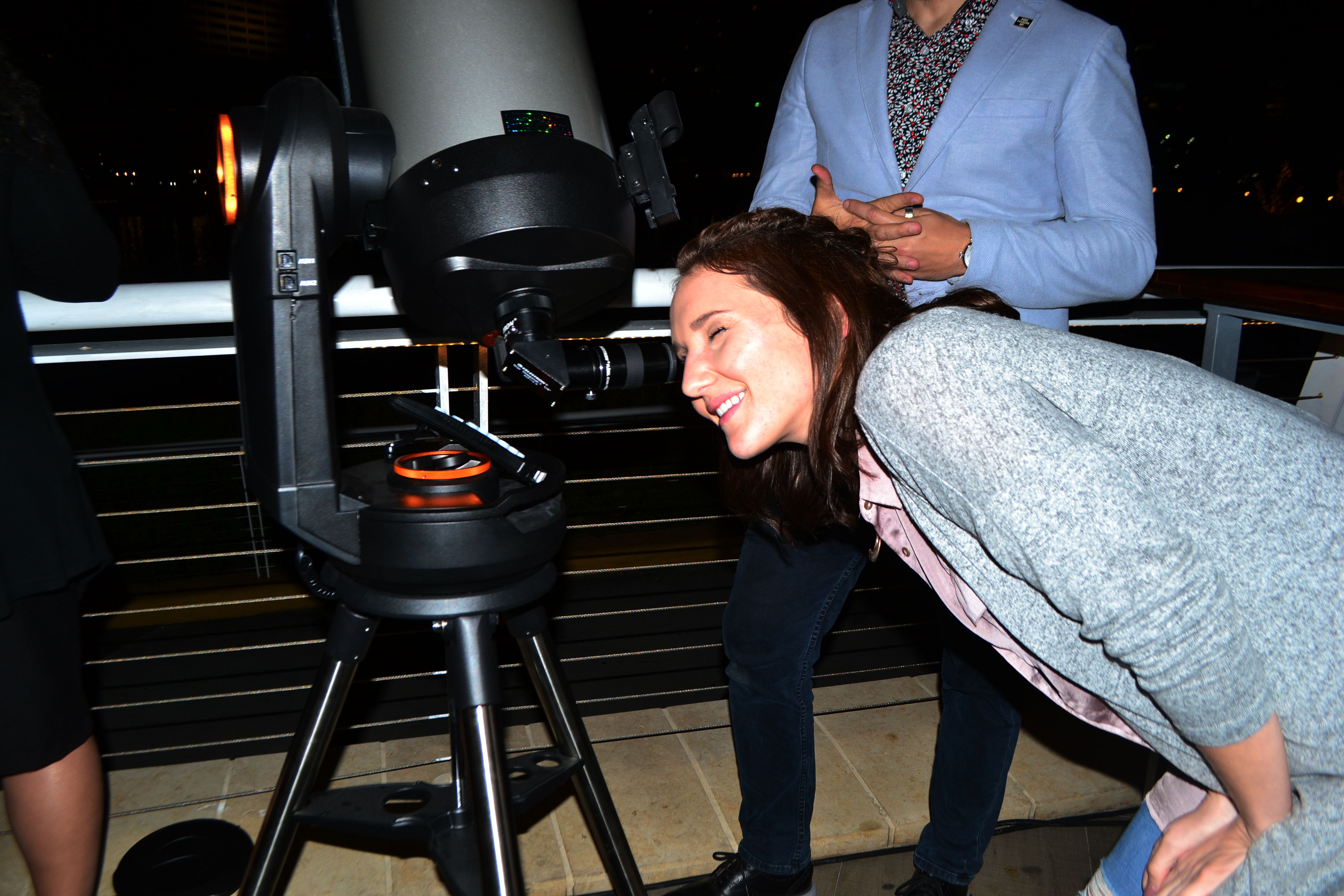 Young Patron enjoying stargazing during happy hour event