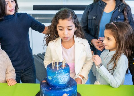 Young girl blowing out the candles on cake at her birthday party.