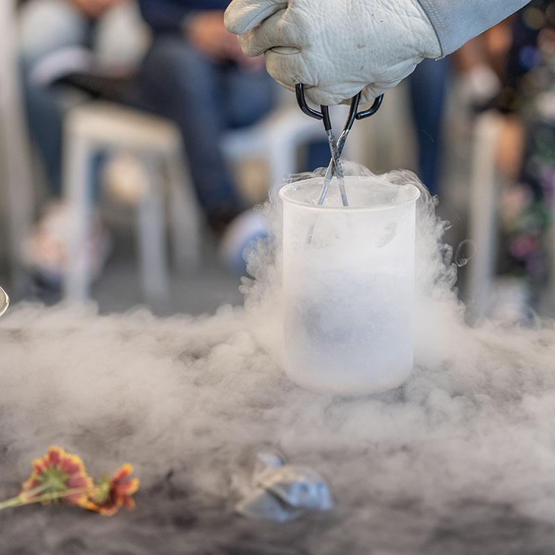 Person using tongs to remove objects from a beaker filled with liquid nitrogen.