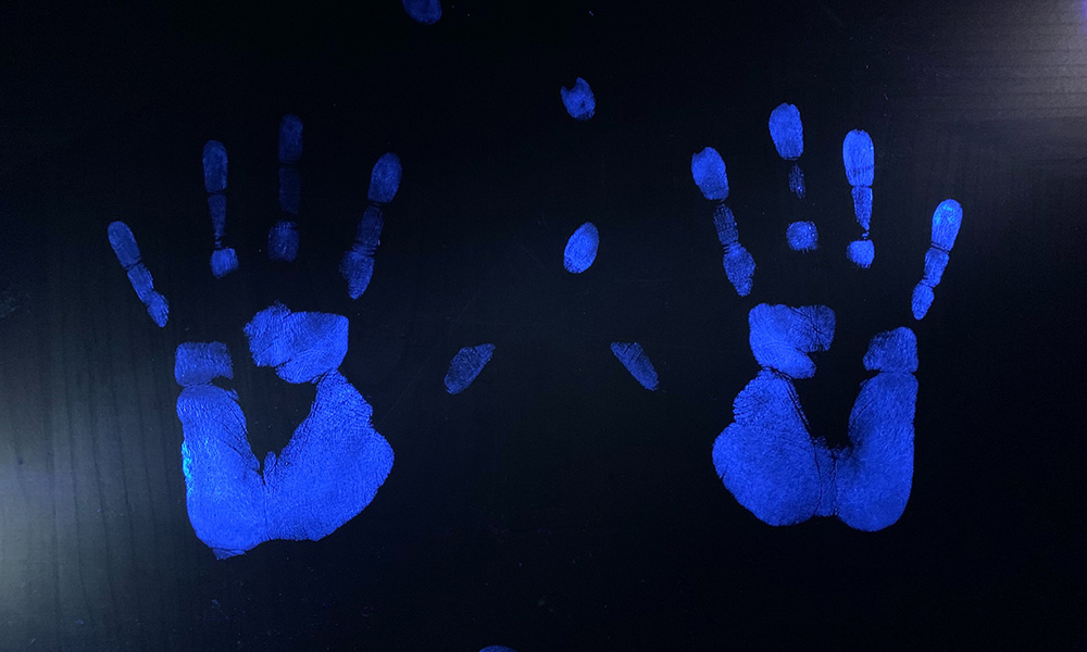 Two Glo Germ hand prints illuminated with uv light