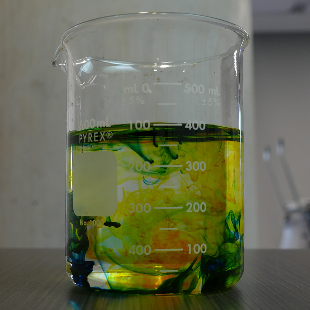 Glass beaker containing water tinted with various colors