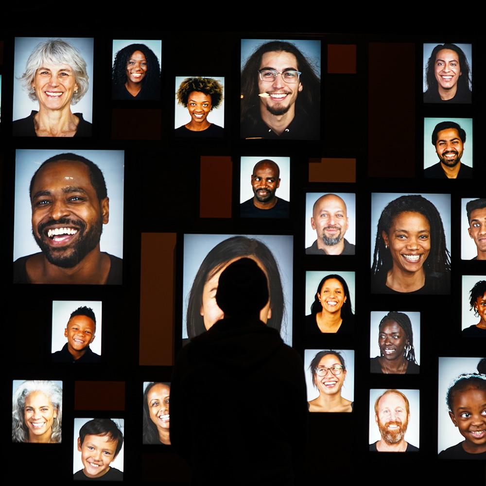 Wall of photos of faces in Photo of Skin: Living Armor, Evolving Identity exhibition.