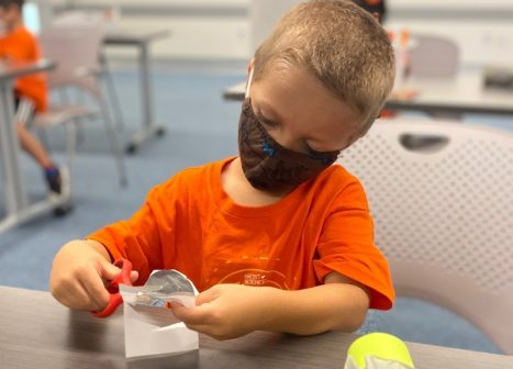child in classroom cutting paper