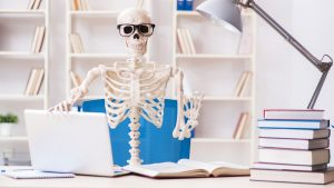 Skeleton waving on the laptop and nerd glasses